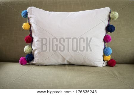 Front View Of White Pillow With Colorful Pompoms On Sides
