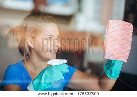 People, Housework And Housekeeping Concept - Happy Woman In Gloves Cleaning Window With Rag And Clea