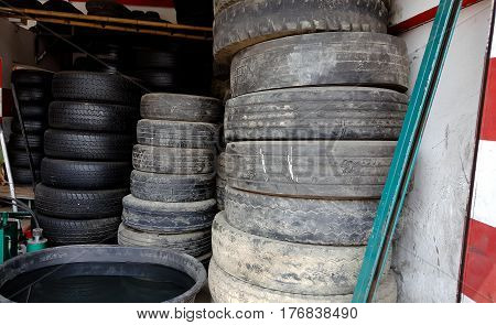 Column stack of old used car tires in secondary car parts shop garage