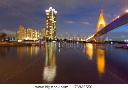 Abstract blurred light office building and bridge cross river with reflection abstract background