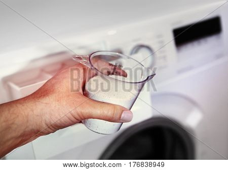 hand of woman that fills detergent in the washing machine