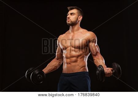 Handsome athletic man in gym is pumping up muscles with dumbbells in a gym. Fitness muscular body isolated on dark background