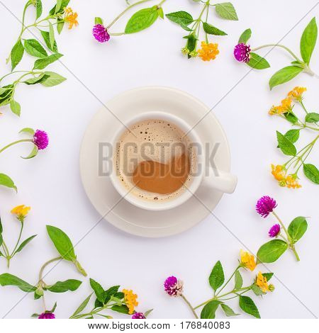 Meadow flowers and wildflowers arranged in circle with coffe cup. Flat lay.