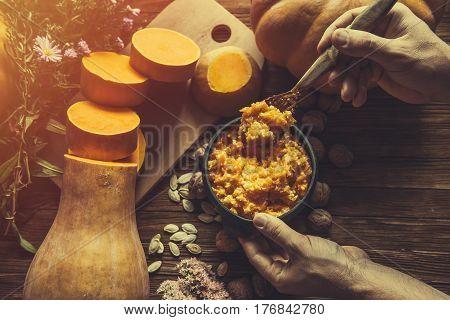 Porridge pumpkin in a clay bowl on wooden background. Pumpkin millet porridge with pumpkin in the background. Still life