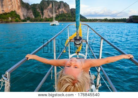 Joyful child portrait. Happy little baby girl on board of sailing yacht have fun discovering islands in tropical sea on summer coastal cruise. Travel adventure yachting with kids on family vacation.