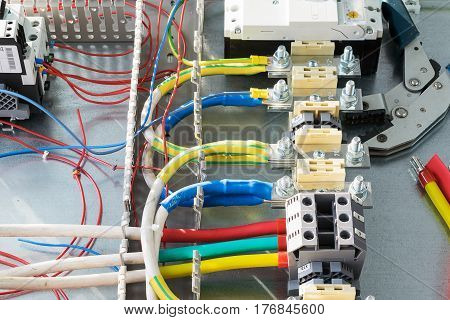 On the mounting panel of the electrical Cabinet fixed bushing terminals bolt and screw. Circuit breaker. Wires and cables with lugs attached to the terminals and the circuit breaker. Relay and the gray cable channels.