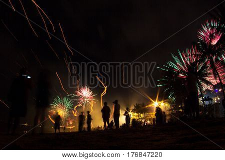 People celebrate holiday on the beach with fireworks
