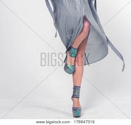 Pretty woman posing in white swimwear and grey bathrobe.