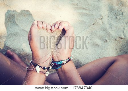 Relaxation and Leisure in Summer lifestyle image of slim tanned girl on beach holding a sand heart symbol in hand. On hands many seashell bracelets. Tropical island beach