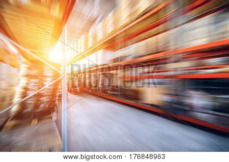 Warehouse industrial and logistics companies. Long shelves with a variety of boxes and containers. Motion blur effect. Bright sunlight.