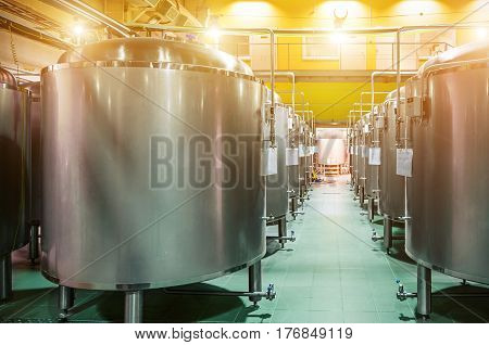 Modern Beer Factory. Rows of steel tanks for the storage and fermentation of beer. Spot light effect