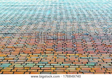End brick wall of the big house. Bricks of different colors. Red orange green blue. Brick wall gets in the future. The cement joints between rows of bricks bonded structure.