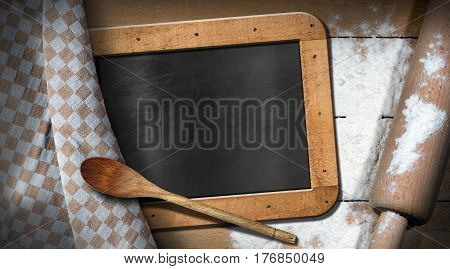 Empty blackboard and label with copy space on a table with white flour wooden rolling pin spoon and brown and white checkered tablecloth