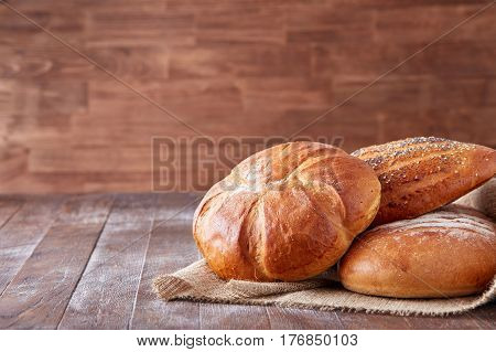 Fresh hot bread in a linen towel on a brown wooden table. free space for writing text. menu. advertising. Bakering. Food and pastries. Bakery.