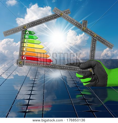 Hand with work glove holding a metal ruler in the shape of house with energy efficiency rating above the solar panels. Concept of ecological house project