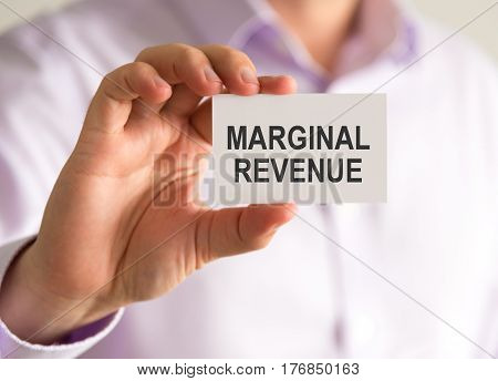 Businessman Holding A Card With Marginal Revenue Message