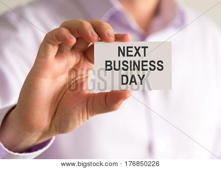 Businessman Holding A Card With Next Business Day Message