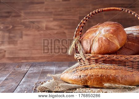 Wicker basket with bread. Bread and buns inside basket. Fresh bakery products on table. Tastes best when warm. On the wooden table with flour. Brown background. Bread on the cloth linen.