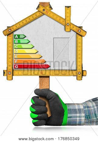 Hand with work glove holding a wooden ruler in the shape of house (sign) with energy efficiency rating. Isolated on white background