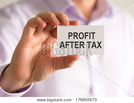 Businessman Holding A Card With Profit After Tax Message