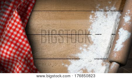 Wooden rolling pin with white flour on a wooden table with copy space and a red and white checkered tablecloth