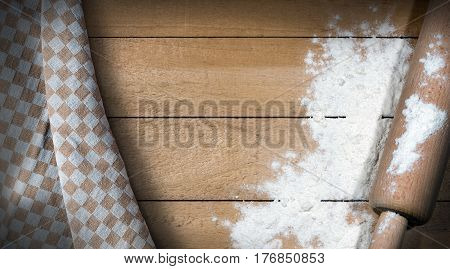 Wooden rolling pin with white flour on a wooden table with copy space and a brown and white checkered tablecloth