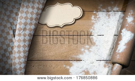 Rolling pin with white flour on a wooden table with an empty label with copy space and a brown and white checkered tablecloth