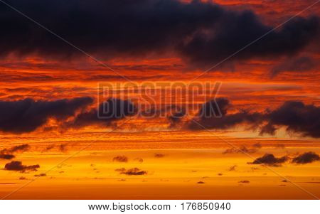 Bright orange sky with clouds at sunset