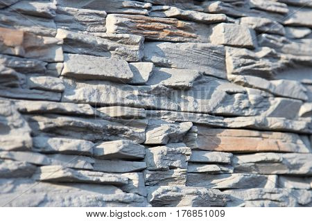 Wall of decorative stone in gray. Shallow depth of field, abstract background.