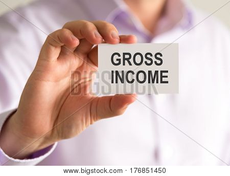 Businessman Holding A Card With Gross Income Message