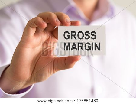 Businessman Holding A Card With Gross Margin Message