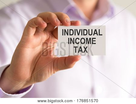 Businessman Holding A Card With Individual Income Tax Message