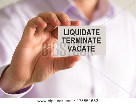 Businessman Holding A Card With Liquidate, Terminate, Vacate Message