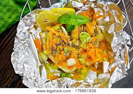 Pike With Carrots And Basil In Foil On Board Top