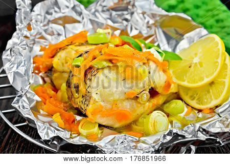 Pike With Carrots And Lemon In Foil On Dark Board