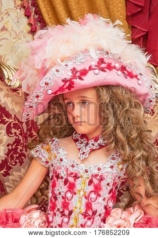 Portrait of sad little girl in carnival costume in style of rococo