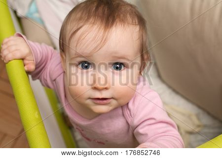 cute caucasian female baby funny face and blue eyes look closeup