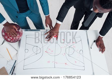 Two african basketball coaches plan and discuss new game strategy. Trainers making scheme of basketball game on the white board.