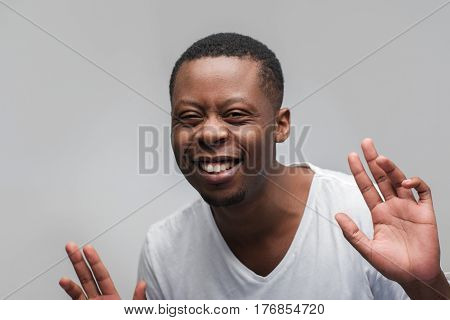 Smiling african american man full of joy. Happiness, laugh, good luck. Headshot portrait on grey background with free space.