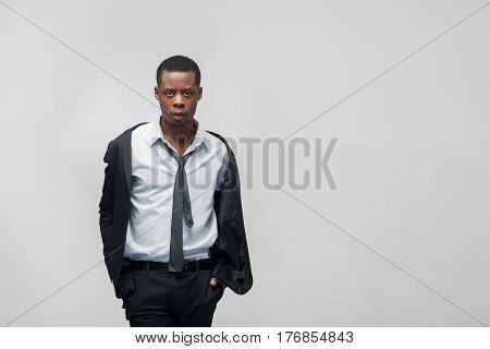 Fashion show, collection of designed clothes. African american guy model in elegant suit on grey background with copy space.