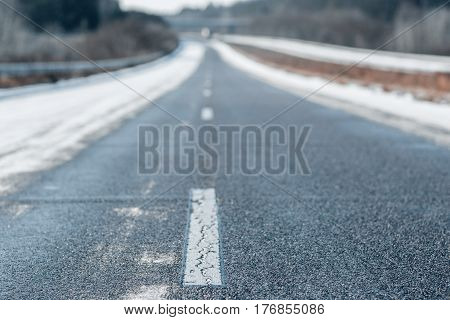 Winter empty highway with a dashed white line in a daytime. Blurred background of winter urban highway landscape.