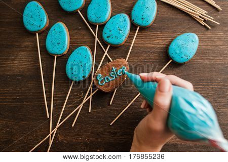 Making easter blue cake pops on wooden rustic table. Cookery art for decoration.
