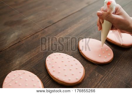 Decorating wedding sweets and desserts with icing. Pink cookies with white icing on rustic wooden empty table closeup.