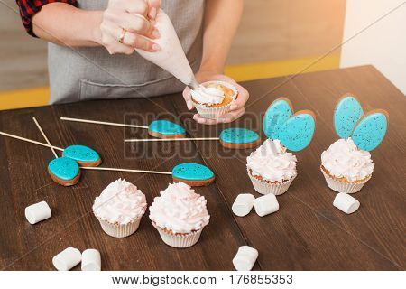 Masterclass of preparing cupcakes with white cream on wooden table. Cookery arts. Easter gift, small business, delivery of sweets, craftmanship concept