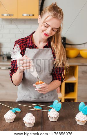 Young woman cooking homemade cup cakes in kitchen. Culinary masterpiece. Gift, small business, delivery of sweets, craftmanship concept