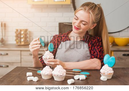 Girl decorating cup cakes with white cream and blue cake-pops at kitchen wooden table. Culinary masterclass. Easter gift, small business, delivery of sweets, craftmanship concept