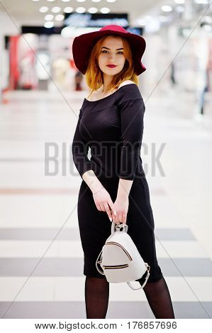Fashion Red Haired Girl Wear On Black Dress And Red Hat With Ladies Backpack Posed At Trade Shopping