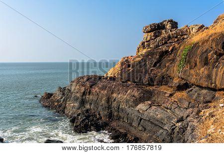 Beautiful seashore with sea wave over rocks. Turquoise clean seawater. White wavy foam of sea surf. Natural scene Gokarna India