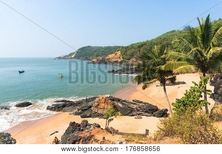 Paradise beach in Gokarna India. Beautiful deserted landscape with clean sand and wave. View from the sea to the shore.