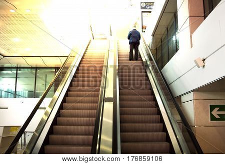 a man is staying on the escalator in the airport